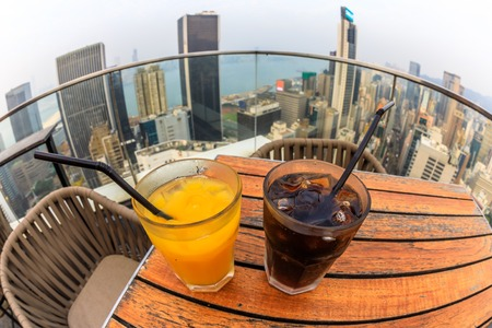 cocktail with city skyline view at dusk from skybar. fisheye angle of coke and juice close up. Stock Photo