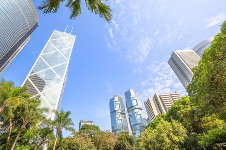 Skyline of modern skyscrapers and towers in the Central business district in a sunny day with blue sky seen from the Hong Kong Park, an oasis of peace in Hong Kong island. Editorial