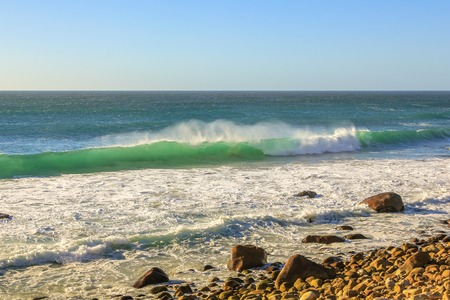 Strong wind and turquoise waves breaking on rocks in Hout Bay, Cape Town, South Africa in the summer season. In winter, Hout Bay is home to big waves for experienced surfers. Stock Photo