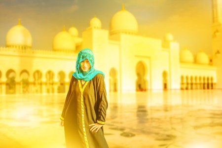 Woman with typical Arab clothes visiting the main attraction of Abu Dhabi and the largest mosque in the UAE. Sheikh Zayed Grand Mosque at sunset. Defocused background. Tourism Middle East concept.