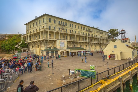 prison guard: San Francisco, United States - August 14, 2016: Panorama of Historic landmark of Alcatraz prison with officers club, water tower, guardhouse, guard tower, theater, ranger station, bookstore and dock.