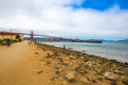 actividades recreativas: San Francisco, California, United States - August 17, 2016: Golden Gate Bridge with fog from Crissy Field popular beach park for locals and tourists. Leisure and recreational activities concept. Editorial