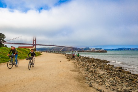 actividades recreativas: San Francisco, California, United States - August 17, 2016: bike tourists at Crissy Field overlooking on Golden Gate Bridge, icon of San Francisco. Leisure and recreational activities concept. Editorial