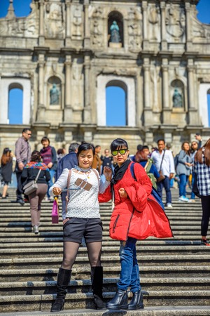 st pauls: Macau, China - December 8, 2016: tourists take a selfie on staircase of Ruins of St. Pauls in a sunny day.The iconic stone facade, on background, one of the most popular historic attractions in Macau Editorial
