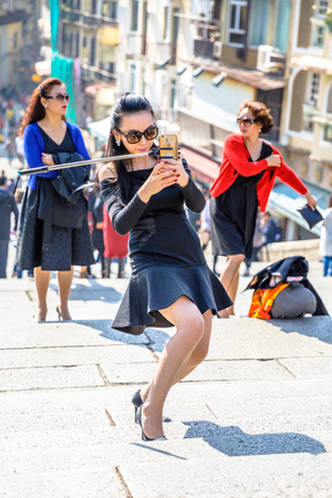 st pauls: Macau, China - December 8, 2016: asian woman with branded clothes and luxury accessories take a selfie on staircase of Ruins of St. Pauls in historic Macau, a popular tourist destination.
