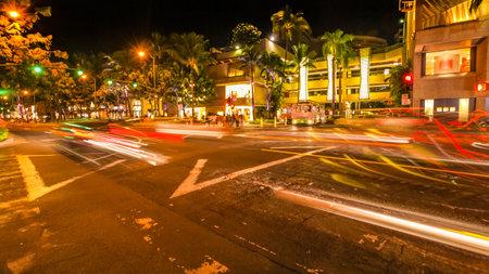 HONOLULU, OAHU, HAWAII, LOS EEUU - 21 DE AGOSTO DE 2016: los coches que cruzan la avenida de la avenida y de la playa de Kalakaua en la falta de definición de movimiento con las calles se encienden. Vida nocturna urbana y concepto de compras.