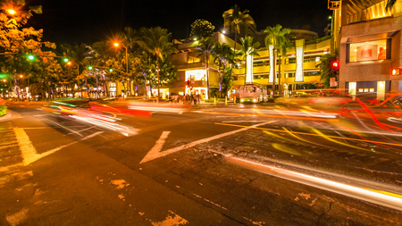 HI: HONOLULU, OAHU, HAWAII, USA - AUGUST 21, 2016: cars crossing the Kalakaua Ave and Seaside Ave crossroad in motion blur with streets lights. Urban nightlife fun and shopping concept.