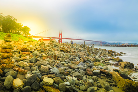 Stone sculptures on the Crissy Field beach park with Golden Gate Bridge. People in leisure and recreational activities. San Francisco, United States