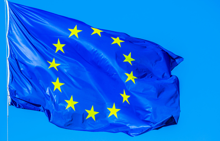 blue Europe flag waving in the wind on blue sky. Stock Photo