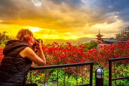 Travel woman photographer with professional camera takes shot of Kiyomizu-dera Temple with red pagoda at sunset light in spring time. Scenic aerial cityscape of Kyoto, Japan. Asian traveler concept. Stock Photo