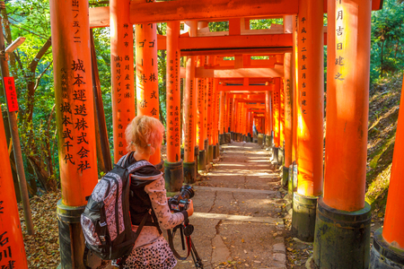 Travel woman photographer with professional camera takes shot of famous landmark Fushimi Inari shrine, south of Kyoto, Japan. Travel asia concept. Kyotos popular landmark. Stock Photo