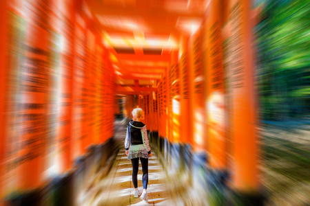 Buddhist temple defocused background. Adventure, exploration, travel concept. Woman walking under red torii gates with blurred motion effect. Fushimi Inari shrine, Kyoto, Japan. Stock Photo