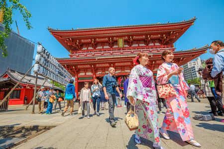 Tokyo, Japan - April 19, 2017: young women in traditional japanese kimonos at south face of the Hozomon, Treasure-House Gate, entrance of Buddhist Temple Senso-ji, Asakusa, the oldest temple in Tokyo.