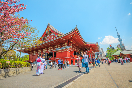 Tokyo, Japan - April 19, 2017: Tokyo icons: Kannon Temple in Senso-ji the oldest shrine in Tokyo, Tokyo Skytree symbol of city, cherry blossom, national flower of Japan and women in japanese kimonos. Editorial