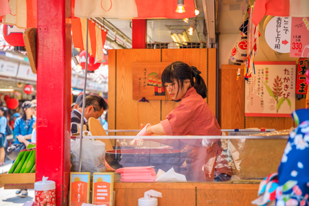 Tokyo, Japan - April 19, 2017: yung asian girl selling Kibidango made with millet flour in famous stand by the pink and bunny theme on Nakamise-dori street at Senso-ji Buddhist Temple, Asakusa.