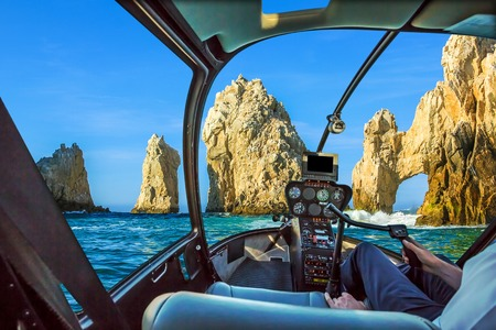 Los Arcos rock formation at Lands End in Cabo San Lucas, Baja California Sur, Mexico. Helicopter cockpit with pilot arm and control console inside the cabin. Summer and holidays concept.