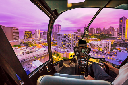 Pink light at twilight of Waikiki cityscape in Oahu island, Hawaii, United States. City night lights and nightlife concept. Helicopter cockpit with pilot arm and control console inside the cabin. Stok Fotoğraf