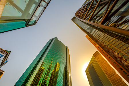 Tokyo, Japan - April 20, 2017: Sky High-rise Facade reflecting. Panoramic wide angle view and perspective to steel light background of glass high rise buildings of Shiodome in Shimbashi. Sunset light. Editorial