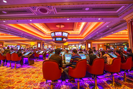 Macau, China - December 9, 2016: people visit The Venetian Casino hall with game machines. The Venetian is the largest casino in the world and the largest single structure hotel building in Asia. 報道画像