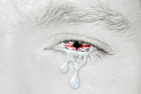 Crying eye with United Kingdom Flag iris on black and white face. concept of sadness for English pain, war and terrorist attack, patriotic metaphor