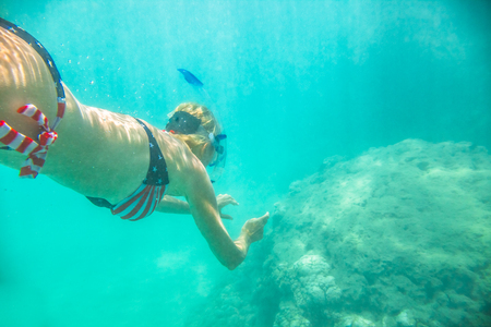 Woman snorkeler swims in tropical sea with american flag bikini. Underwater scene of a female apnea and doing skin diving. Watersport activity in Hawaii. Tropical destination holiday travel. Stock Photo