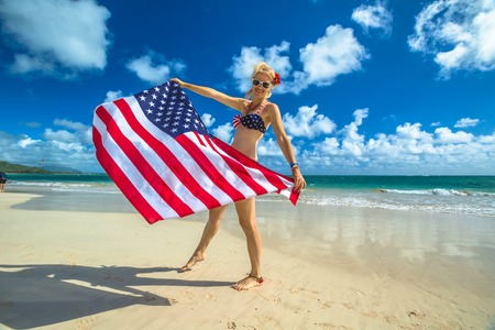oahu: Smiling woman with american flag bikini waving american flag in spectacular tropical Lanikai Beach, east shore of Oahu in Hawaii, USA. Enjoying and freedom in Hawaiian vacations. Patriotic concept.