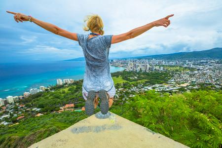 Happy hiker jumping. Hawaiian hiking by popular Diamond Head hike. Traveler freedom woman. Honolulu and Waikiki Beach Skyline from Diamond Head State Monument and Park. Oahu Island in Hawaii, USA.