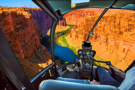 Helicopter cockpit with pilot arm and control console inside the cabin on the Grand Canyon Lake Powell. Reserve on the Colorado River, straddling the border between Utah and Arizona. USA, America. Фото со стока