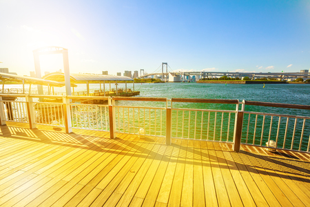 water bus: Sunset promenade walkway and jetty where waterbuses and ferry boats arrive at Odaiba Seaside Park in Odaiba island, Tokyo, Japan. Urban cityscape of Rainbow Bridge with Tokyo Skyline on background.
