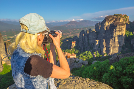 kalabaka: Traveler woman photographer with professional camera takes pictures of monasteries of Meteora in Central Greece, Europe. Caucasian female photographing a popular greek landmark. Europe travel.