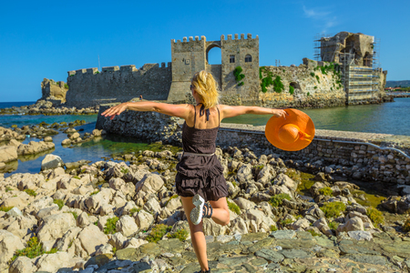 Happy tourist vacation woman with sun hat in the air enjoying on islet of Bourtzi. Methoni Venetian Fortress, a medieval fortification, Peloponnese, Greece. Happiness travel holidays lifestyle concept Stock Photo