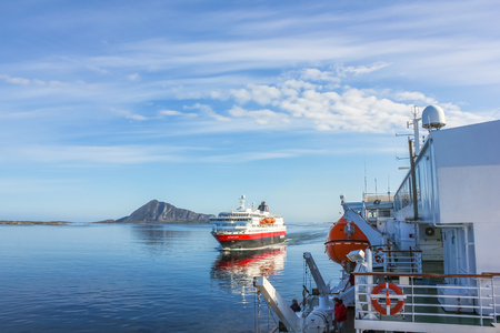 ms: Norway, Europe - May 4, 2011: Two Hurtigruten sail in Norwegian waters. Norwegian postal boat crosses MS Richard With, in Norwegian Fjords of Lofoten Islands. Cruise ship holidays in Norwegian Coast. Editorial