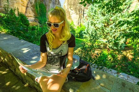 Travel Greece tourist woman on Europe looking at map outdoors. Blond caucasian happy female holding travel map at St. Nicholas Anapafsas Monastery in Meteora, Thessaly, Greece. Tourism people concept. Stock Photo