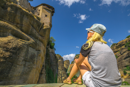 Caucasian beautiful blonde tourist looking up the St. Nicholas Anapafsas Monastery in Meteora, Thessaly, Greece. Tourism and travel in Europe. Woman traveler in landmark and Heritage Site. Bottom view Stock Photo