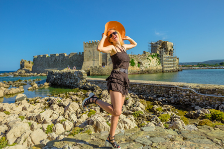 Happy attractive tourist vacation woman with sun hat enjoying on islet of Bourtzi. Methoni Venetian Castle, a medieval fortification, Peloponnese, Greece. Happiness travel holidays lifestyle concept Stock Photo