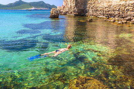 Woman bikini snorkeling around scenic Methoni Castle, a medieval fortification in Methoni, Messenia, Peloponnese, Greece. Female snorkeler swims in crystal water. Summer watersport activity leisure. Stock Photo