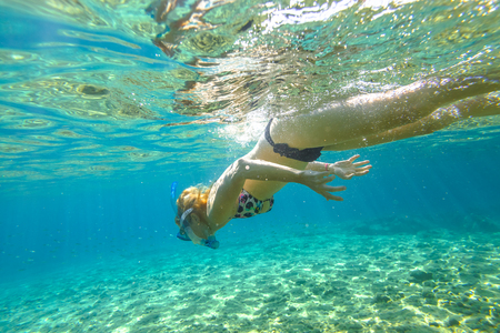 Female apnea bikini swims in crystal sea. Underwater background of a woman snorkeling and doing skin diving. Watersport activity in summer vacations. Tropical destination holidays concept. Stock Photo