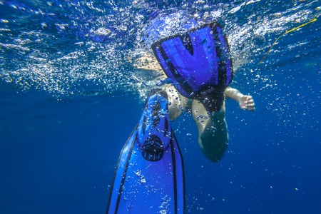 Closeup of blue fins of underwater female apnea while swimming. Bubbles of water. View from behind snorkeler woman in underwater activity. Watersport and leisure concept. Fins slamming into sea. Stock Photo