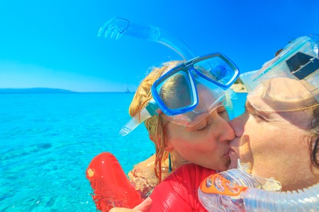Couple with snorkeling equipment kissing in tropical sea.Snorkel couple enjoying in romatic vacations. Summer holidays watersport concept. Leisure and sport in crystal waters.Young couple on honeymoon Stock Photo