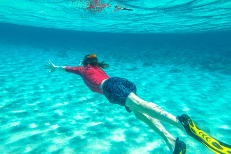 Man with mask snorkeling in clear water. Underwater background of a man snorkeling and doing free diving. Watersport activity in summer vacations. Tropical destination holidays concept. Stock Photo