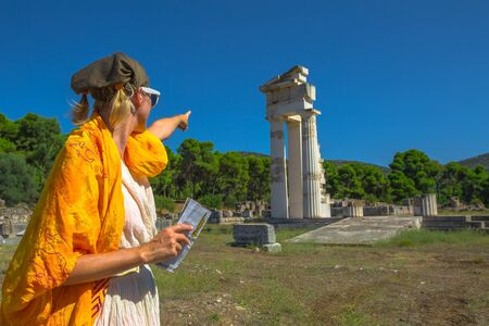 Tourist woman in Greek dress indicates the ruins of Temple of Asklepieion, Epidaurus, Peloponnese, Greece. The Sanctuary of Asclepius is a famous heritage site.Mediterranean travel and tourism concept Stock Photo