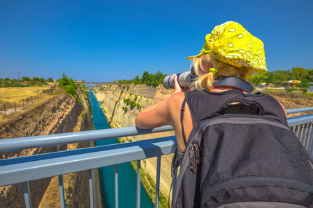 aerial photograph: Travel photographer with telelens takes photos from Bridge of Corinth Channel. Corinth Canal connects the Gulf of Corinth with the Saronic Gulf in Aegean Sea. Female photographer in Greece, Europe.