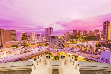 Barefoot girl on top at twilight trying to suicide, over Waikiki cityscape in Oahu island, Hawaii, United States. Depression and stress urban life concept.