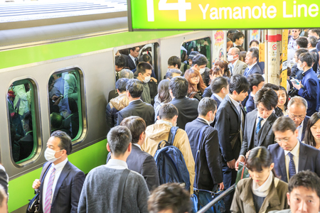 Tokyo, Japan - April 17, 2017: Crowd of commuters ascends and drops from train at rush hour in Shinjuku Station, the citys main station.The Yamanote Line is the most important train line in Tokyo.