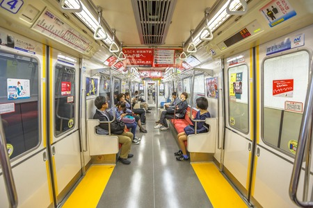 Tokyo, Japan - April 17, 2017: asian people commuter subway wagon interior. The Toei Oedo Line, a subway line in Tokyo. On maps and signboards, the line is shown in magenta and letter E.