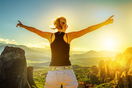 kalabaka: Traveler woman with open arms at sunset in Meteora valley in Thessaly, Greece. Happy female hiker with sun in the face. Panoramic view from best view point Psaropetra. Tourism in Europe. Stock Photo