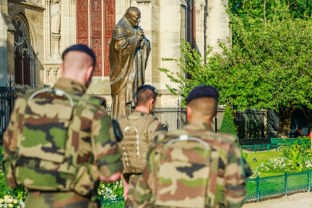 PARIS, FRANCE - JULY 1, 2017: Pope John Paul II statue guarding soldiers of National Armed Forces in Notre Dame of Paris, keeping security after recent terrorist attacks in Paris.
