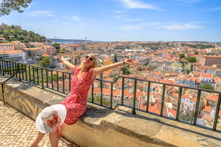 Lisbon views of popular Sao Jorge Castle and 25 April Bridge. Happy tourist woman with open arms at viewpoint Miradouro da Graca. Alfama Quarter in Lisbon, Portugal, Europe. Europe travel concept.