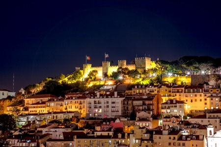Scenic aerial view of Lisbon panorama by night. Architecture background. Details of Sao Jorge Castle or Fortress of Saint George from platform of Elevador de Santa Justa tourist attraction in Baixa.