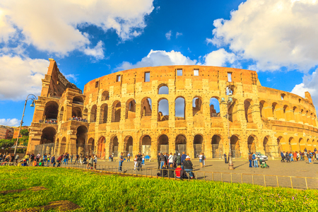 Rome, Italy - May 12, 2016: tourists in front of Colosseo at sunset, Colosseum, Flavian Amphitheatre, the largest amphitheater in the world and one of the symbols of Italy and Rome.